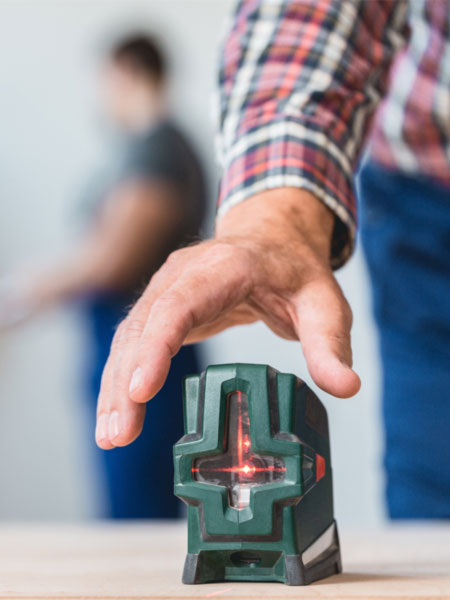 nahaufnahme einer Hand, die mit einem Lasermessgerät arbeitet