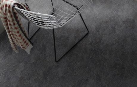 Vinylfliesen Slate Black in schwarzer Natursteinoptik mit Stuhl aus schwarz-weißem Drahtgitter