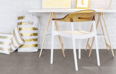 weiße Schreibtischplatte liegt auf zwei Holzböcken und davor steht ein weißer Stuhl mit goldener Lehne