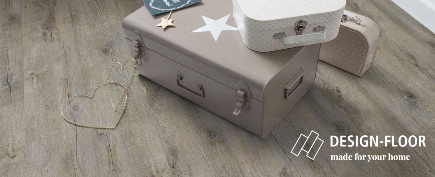zwei dekrative alte Koffer stehen auf einem Vinylboden in beiger Holzoptik