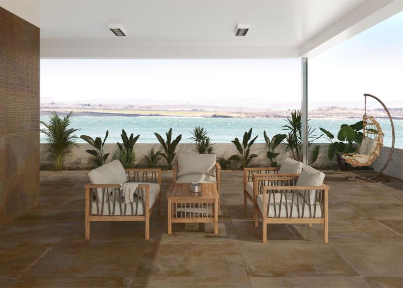 überdachte Terrasse mit Meerblick und Loungemöbeln aus Holz und weißen Polstern
