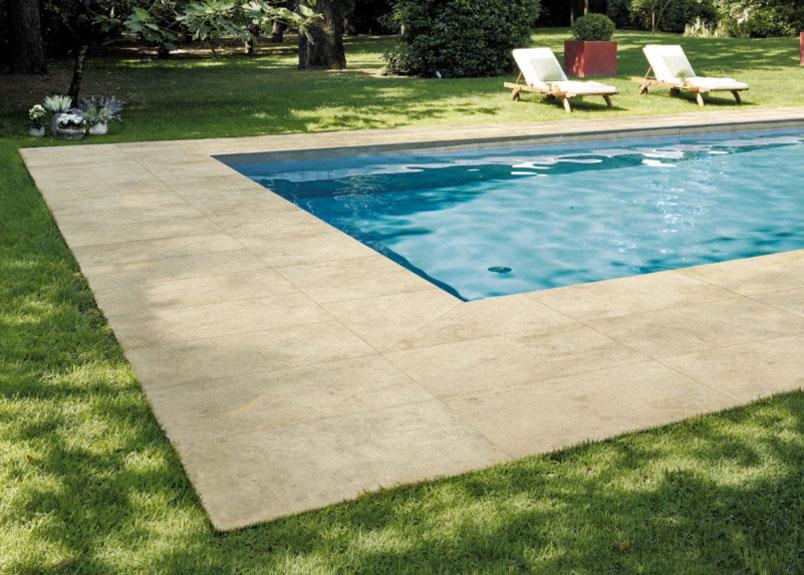 Blick auf Pool und zwei Liegestühle in großem Garten Poolumrandung mit Keramik Terrassenplatten in beiger Kalksteinoptik pureto Provence