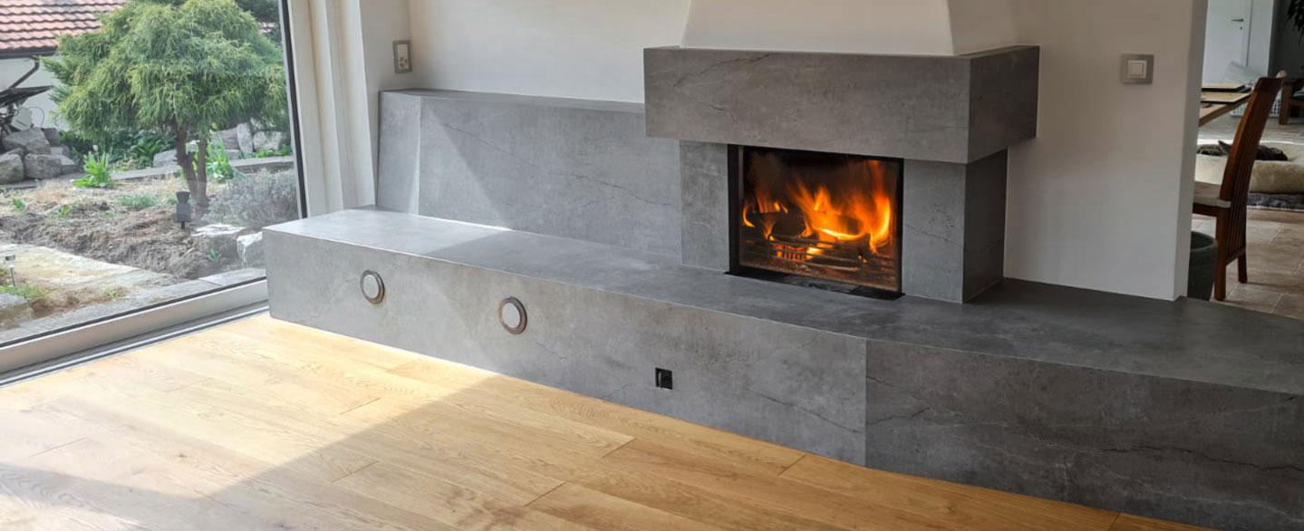moderne, minimalistische Kaminverkleidung und Ofenbank aus Keramikplatten in dunkelgrauer Marmoroptik