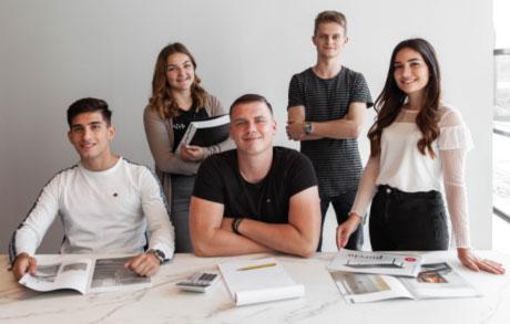 Freundliches Gruppenfoto der fünf Auszubildende Kaufleute für Büromanagement der Dinger Stone GmbH mit Prospekten in den Händen