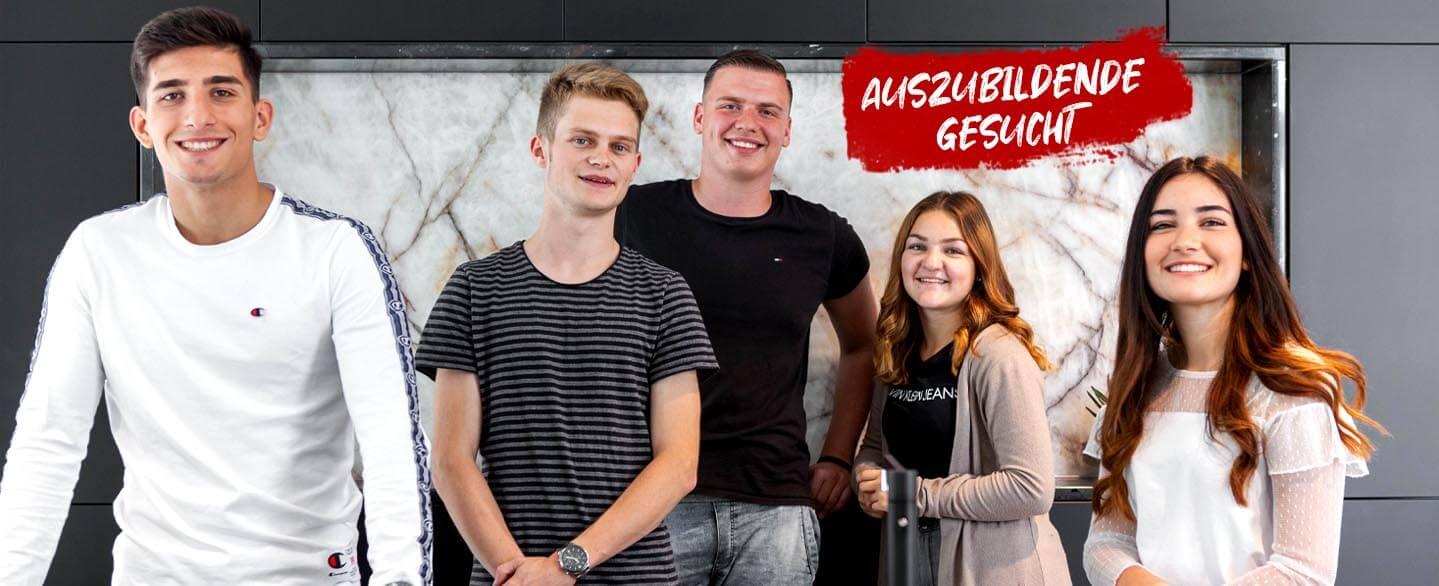 """Gruppenfoto der fünf Auszubildende Kaufleute für Büromanagement bei der Dinger Stone GmbH mit dem Banner """"Auszubildende gesucht"""""""