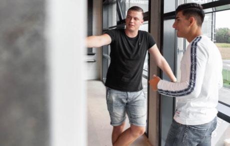 Auszubildender Jannik Dvorak zeigt dem Auszubildenden Fabion Bajgora eine Arbeitsplatte