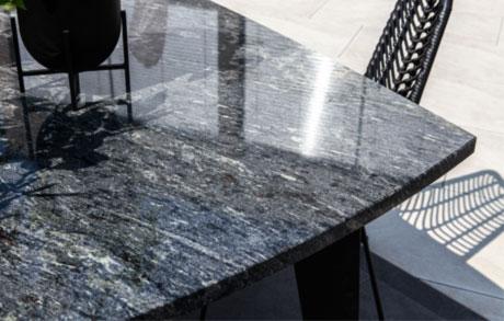 Dunkler Ess- oder Gartentisch aus massivem Naturstein mit dem Namen Azul California