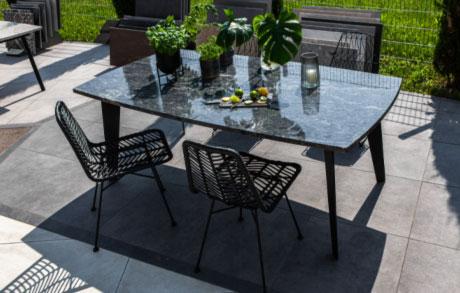 Gedeckter Ess- oder Gartentisch aus dunklem massivem Naturstein mit dem Namen Azul California und vier Stühlen