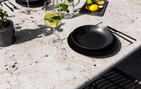 Gedeckter Ess- oder Gartentisch aus hellem massivem Naturstein mit dem Namen Bianco Romano