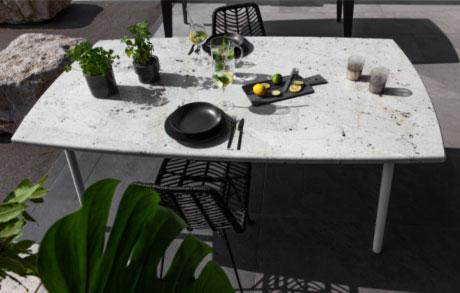 Gedeckter Ess- oder Gartentisch aus hellem massivem Naturstein mit dem Namen Bianco Romano und zwei Stühlen