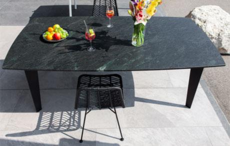 Gedeckter Ess- oder Gartentisch aus dunklem Naturstein mit leicht grünlichen Akzenten welches den Namen Black Musk trägt
