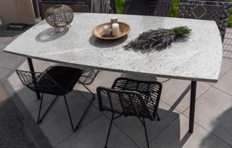 Gedeckter Ess- oder Gartentisch aus hellem Naturstein Ivory Fantasy mit vier Stühlen