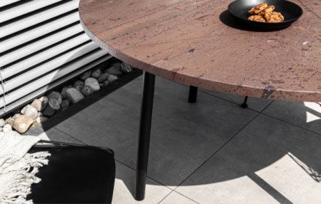 Runder Gartentisch aus braunem Naturstein mit schwarzem Stahlgestell mit dem Namen Terra Lova