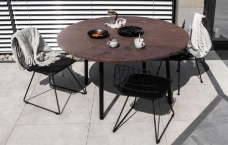 Gedeckter runder Gartentisch aus braunem Naturstein mit schwarzem Stahlgestell und drei Stühlen mit dem Namen Terra Lova