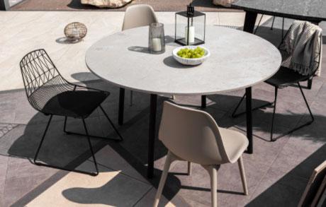 Runder Ess- oder Gartentisch mit frischen grünen Trauben darauf und vier Stühlen